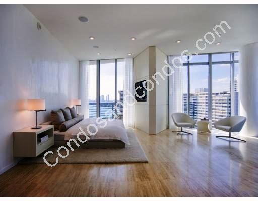 Master bedroom with city view and built-in TV