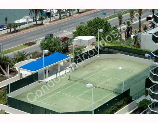 Two lighted tennis courts with a landscaped promenade