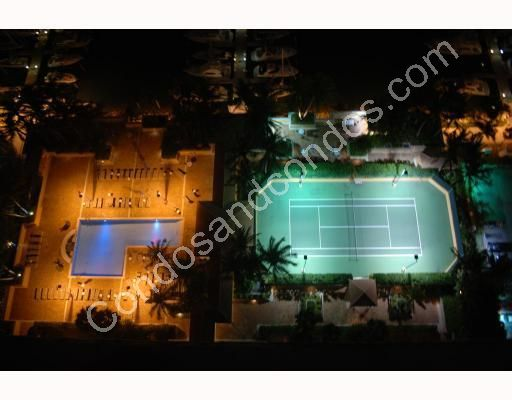 Bayside pool and tennis court illuminated at night