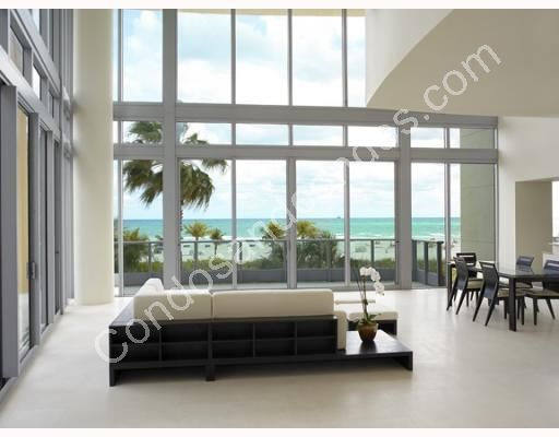 Open living/Dining area with glass walls overlooking the beach