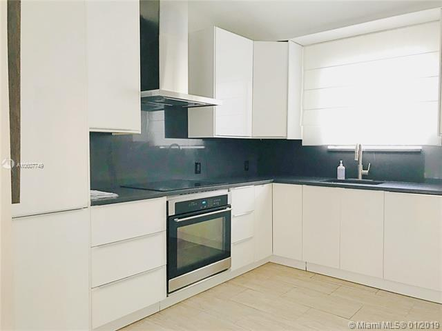 New white kitchen with black stone counters and backsplash and S/S Appliances