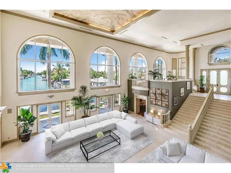Grand two story living room with soaring ceilings and walls of windows.